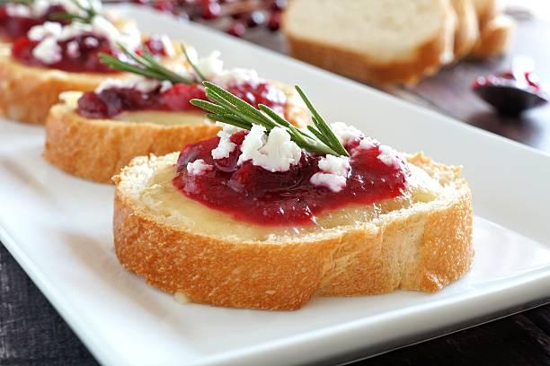 crostini with cranberries, cheese, rosemary close up on white plate - aufstrich weihnachten stock-fotos und bilder