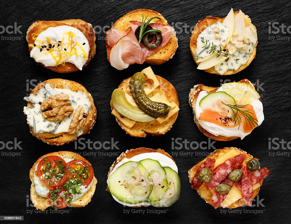 Crostini with different toppings on black background stock photo