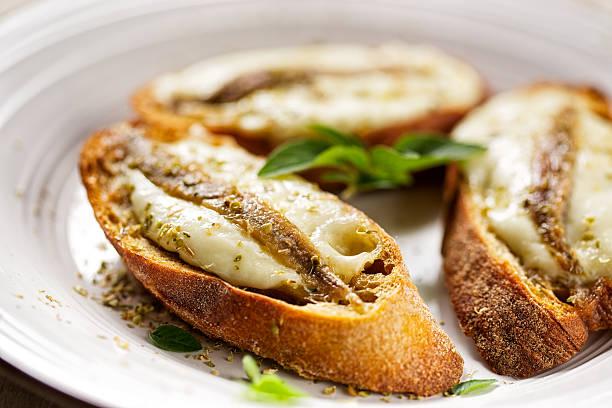 Crostini with fish, mozzarella and oregano Crostini with anchovy fish, mozzarella and oregano anchovy stock pictures, royalty-free photos & images