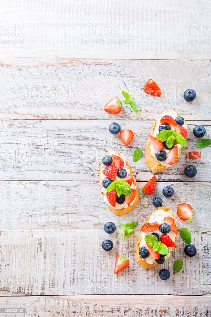 Crostini with grilled baguette, cream cheese and berries royalty-free stock photo