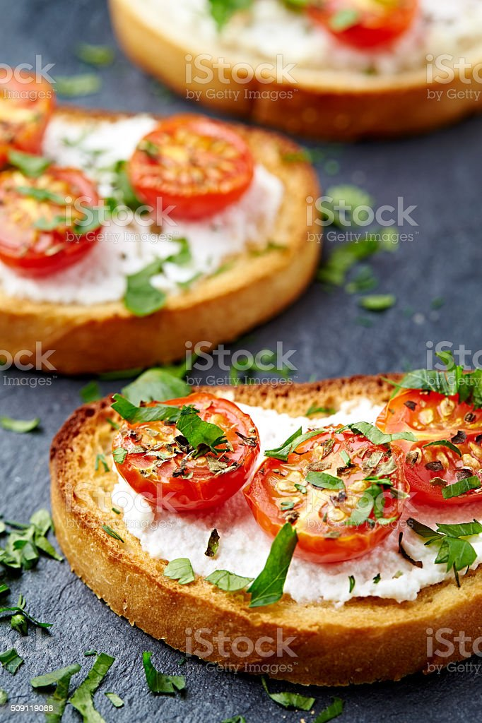 Crostinis with cherry tomato and ricotta stock photo