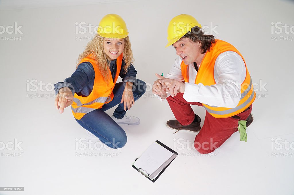 Crouched construction workers, a man and a smiling blonde girl stock photo