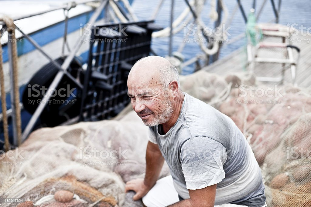Crouched Fisherman On Fishing Net royalty-free stock photo