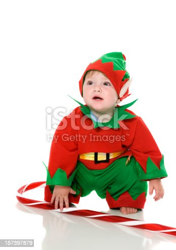 Photo of a little boy in the image of a gnome. Little christmas gnome in a red cap and vest.
