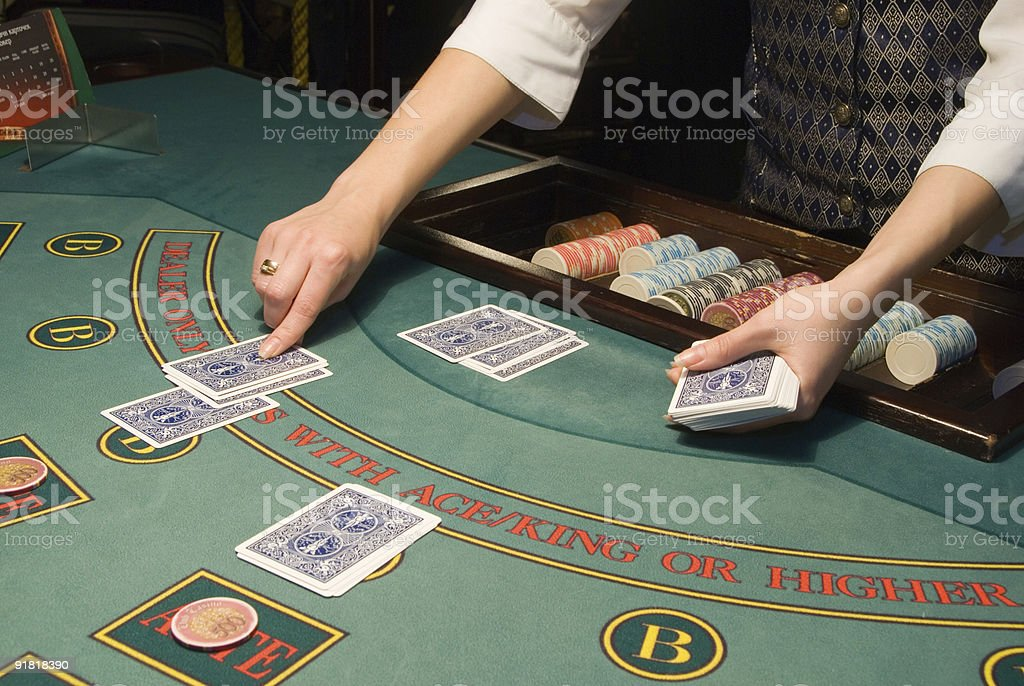 croupier handling cards at poker table stock photo
