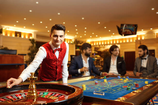 A croupier works at a poker roulette in a casino. stock photo