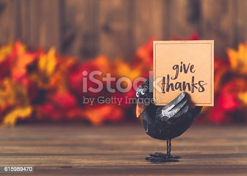 istock Crow with greeting in front of leaves and wood background 615989470