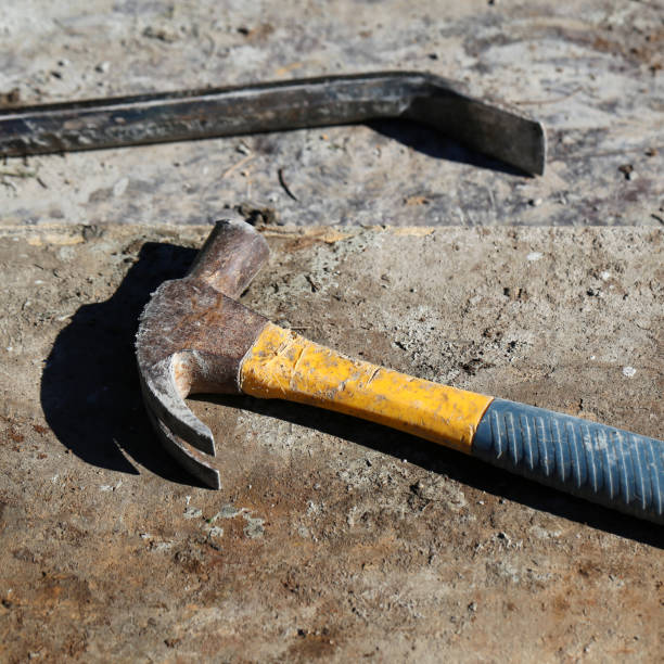 Crowbar and Hammer on a Concrete Surface during a Sunny Day stock photo