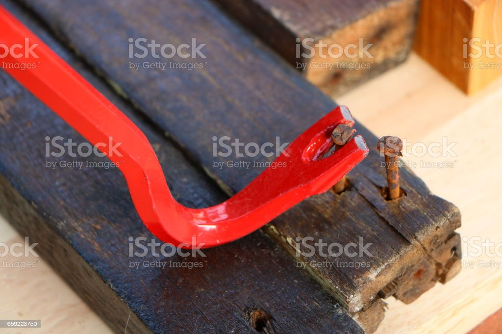 Crowbar pulling a nail to demonstrate the concept of leverage stock photo
