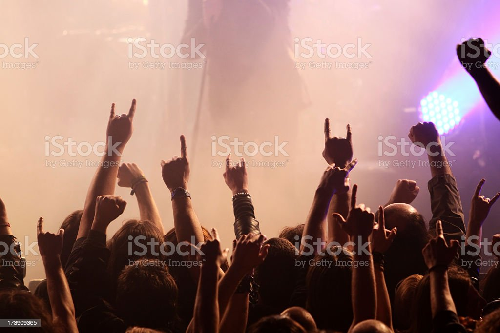 A crowd at a concert lifting rock hands stock photo