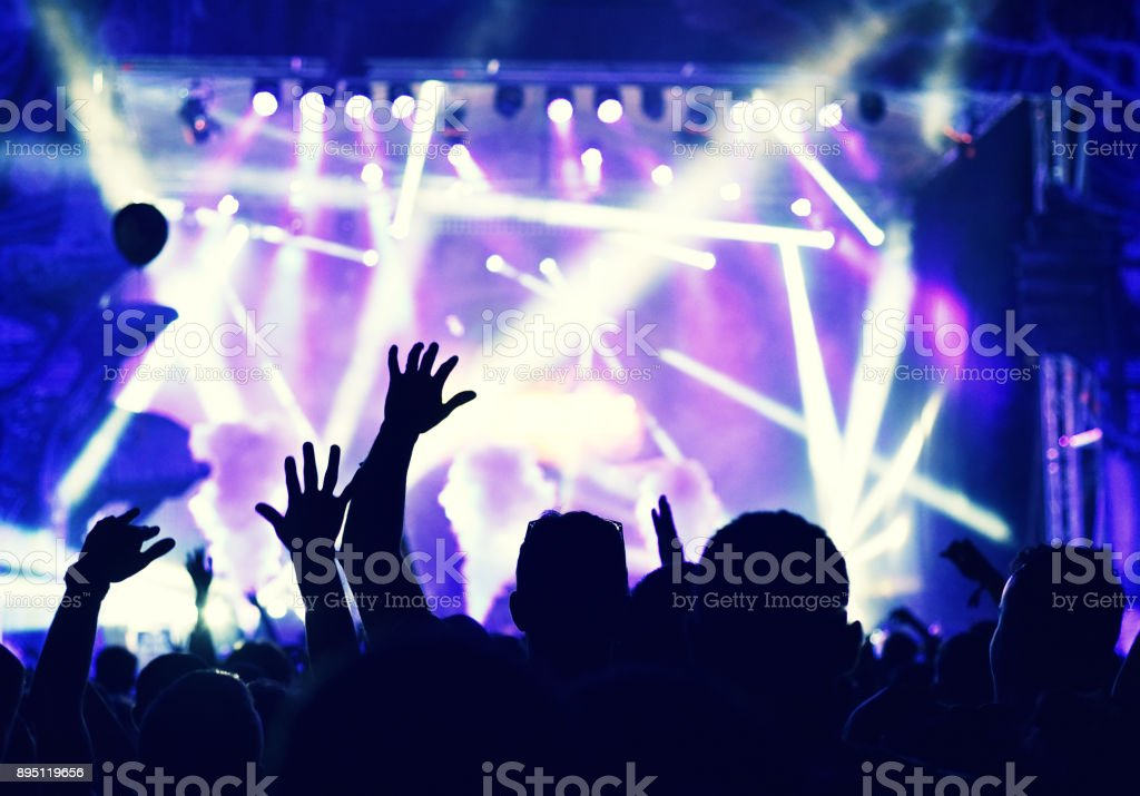 Silhouette of hands on a concert in front of bright stage lights