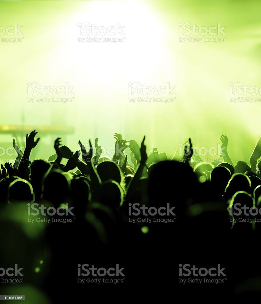 Crowd at concert with lights dimmed and green lights royalty-free stock photo