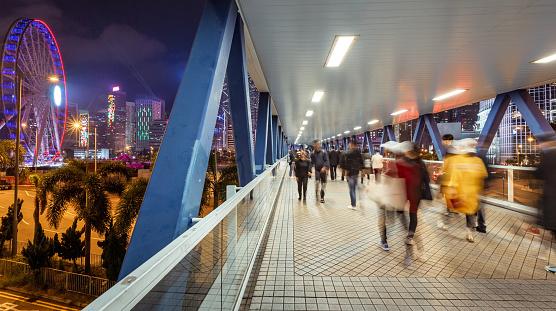 Crowd at public walk way in Hong kong island city at night
