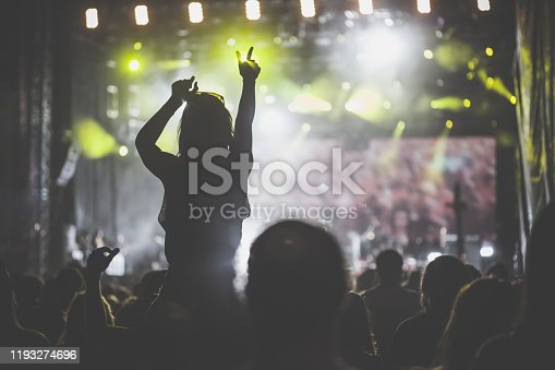Rear view of large group of unrecognizable people cheering, applauding, dancing and having fun while enjoying illuminated rock concert on a music festival. And a woman that is being carried on shoulders is holding her hands in the air.