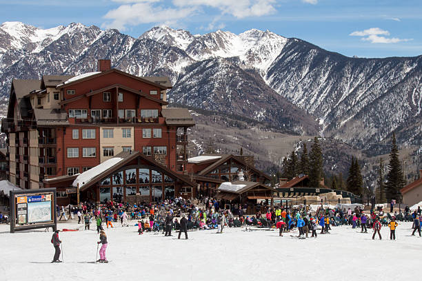"Crowd at ""The Beach"" at Purgatory in Durango, CO Durango, Colorado, USA - March 13, 2016: A crowd of skiers and snowboarders hang out at ""The beach"" at Purgatory ski resort in Durango, Colorado.  The ski lodge backdrop are the majestic, snowcapped San Juan mountains. san juan mountains stock pictures, royalty-free photos & images"