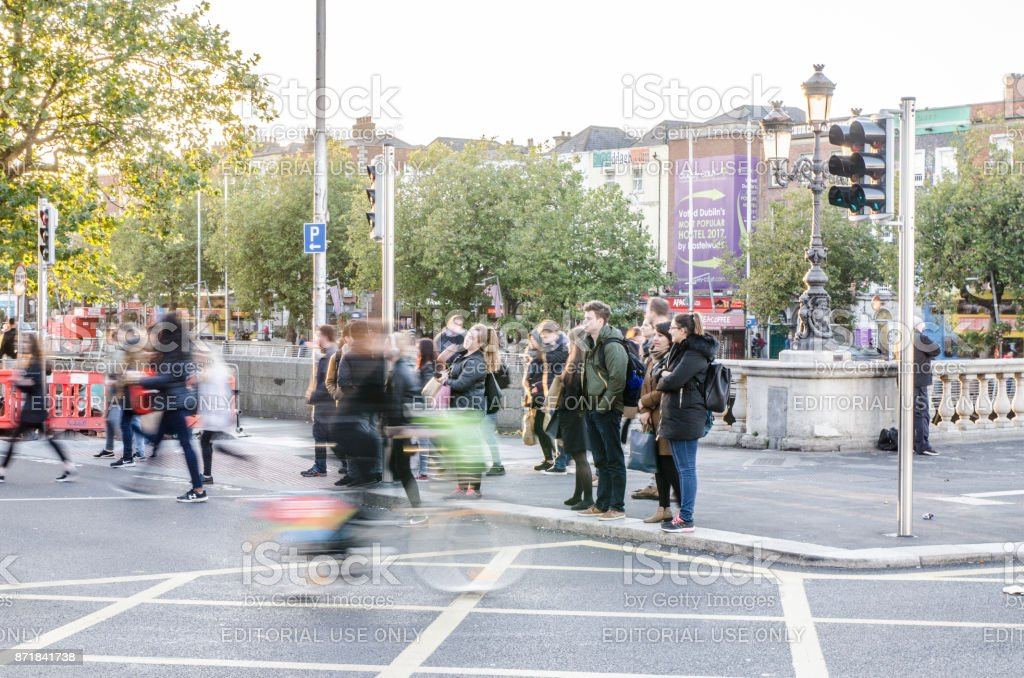 Crowd at the corner of Aston Quay and O'Connell Bridge in Dublin Ireland during day of autumn stock photo