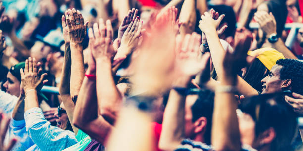 Crowd cheering for their team with arms raised Large crowd in a football stadium cheering for their team with their hands raised and clapping. spectator stock pictures, royalty-free photos & images