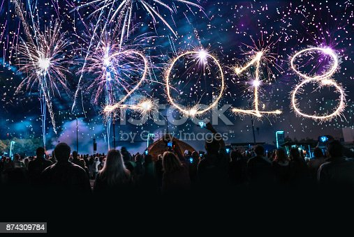 istock crowd cheering in front of firework with 2018 numbers 874309784