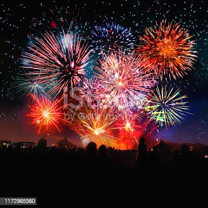 istock crowd cheering in front of vibrant firework 1172965360