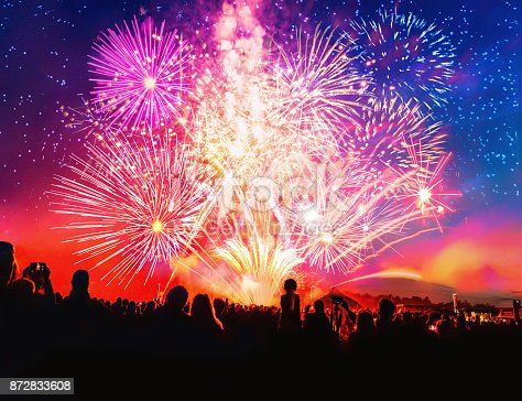 istock crowd cheering in front of vibrant firework 872833608