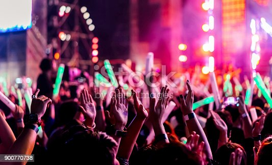 istock Crowd clap or hands up at concert stage lights and people fan audience raising hands silhouette with spotlights glowing effect in the music festival rear view 900770738