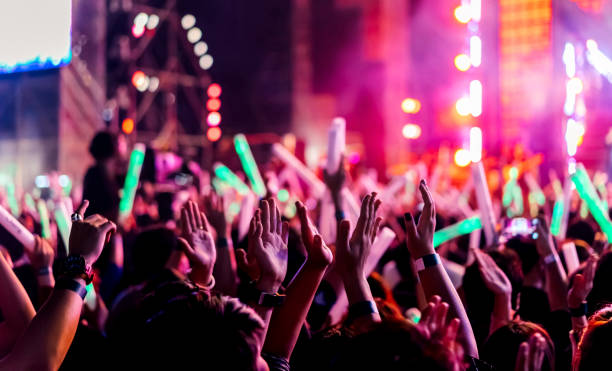 crowd clap or hands up at concert stage lights and people fan audience raising hands silhouette with spotlights glowing effect in the music festival rear view - gmail imagens e fotografias de stock