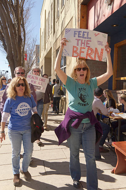 Crowd Feels the Bern in Asheville Asheville, North Carolina, USA - February 28, 2016:  A crowd of Bernie Sanders rally supporters march holding a variety of signs about issues like health care during a campaign rally on February 28, 2016 in downtown Asheville, NC bernie sanders stock pictures, royalty-free photos & images