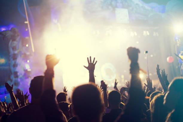 menschenmenge, glückliche menschen genießen rock-konzert, hob die hände - große waffen stock-fotos und bilder
