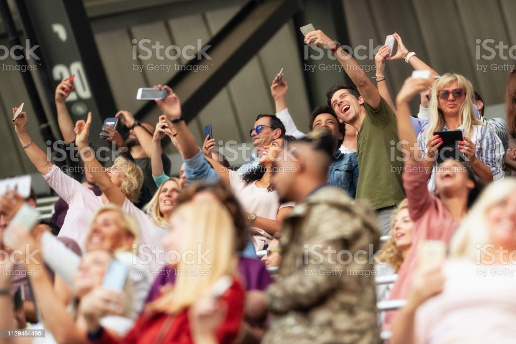 Crowd in a stadium bleachers smiling and taking selfies.