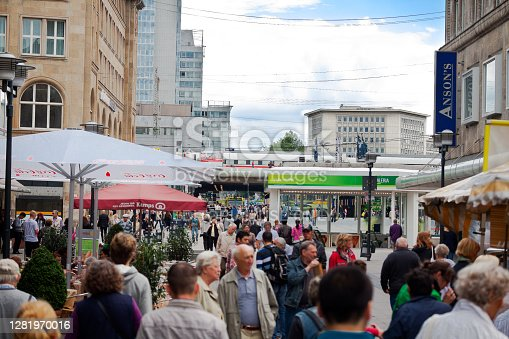 Crowd in city street Kettwiger Strasse in Essen in summer season. View over heads of walking people. In backgroundare office buildings and main station. ICE train is on tracks incoming station
