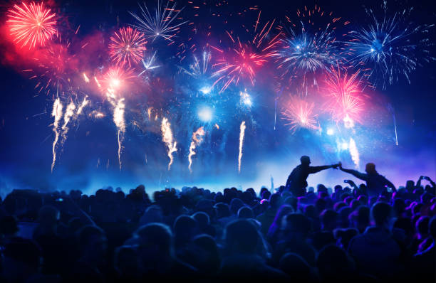 Crowd in front of vibrant firework display stock photo