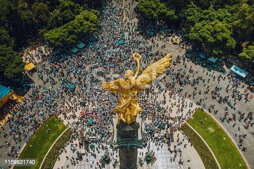 High Angle View Of Crowd Marching On Independence monument in Mexico City.