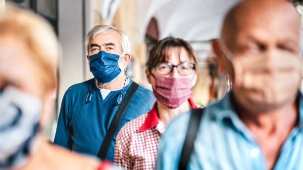 Crowd of adult citizens walking on city street - New reality lifestyle concept with senior people with covered faces - Selective focus on bearded man with blue protective mask stock photo
