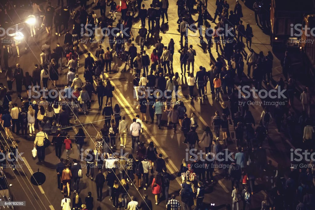 Crowd of anonymous people walking on night Voronezh street, view from...