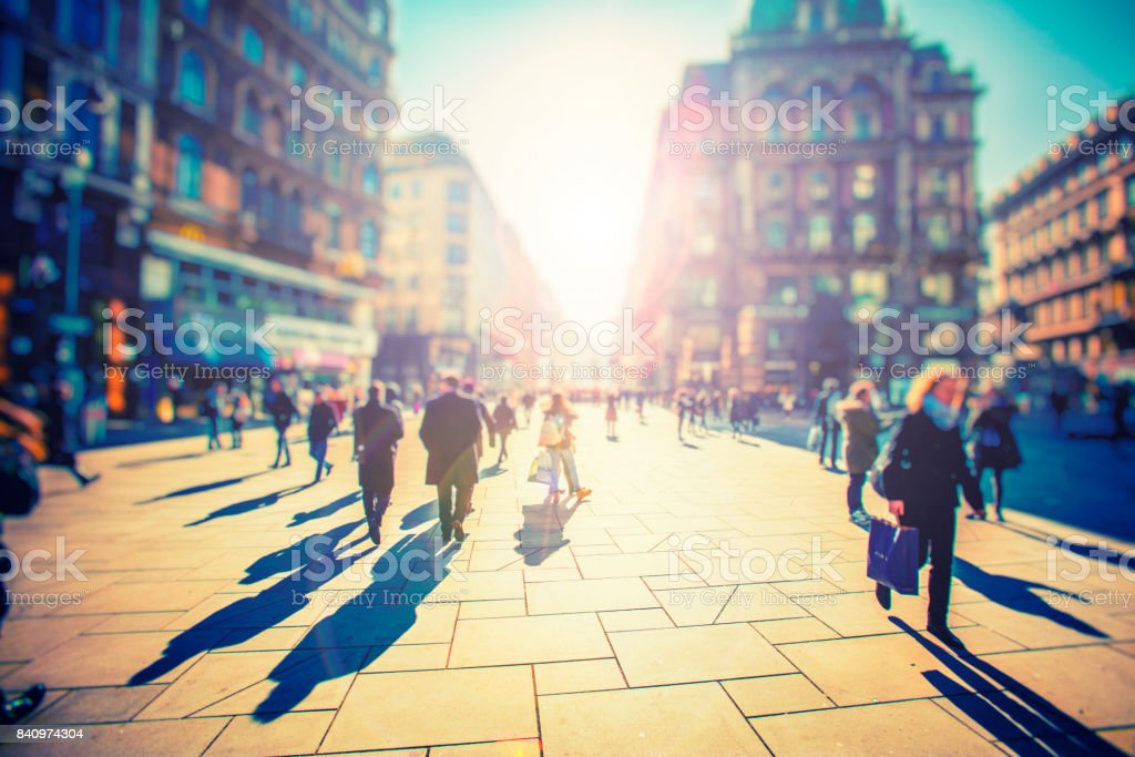 Crowd of anonymous people walking on sunset in the city streets stock photo