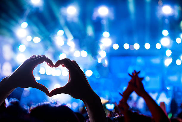 Crowd of Audience at during a concert Crowd of Audience at during a concert with silhouette of a heart shaped hands shadow, light illuminated is power of music concert political party stock pictures, royalty-free photos & images