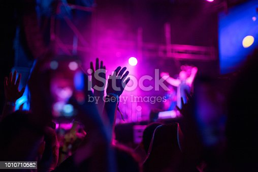 istock Crowd of audience with hands raised at a music festival. Lights streaming down from above the stage 1010710582