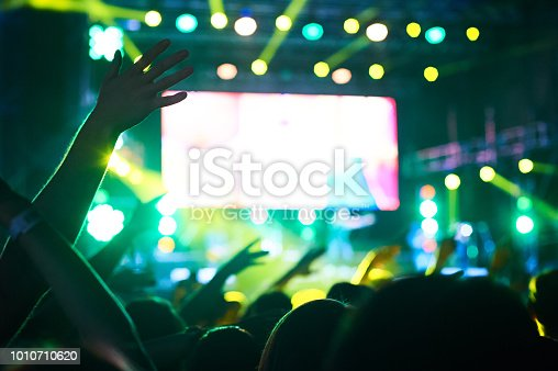 istock Crowd of audience with hands raised at a music festival. Lights streaming down from above the stage 1010710620