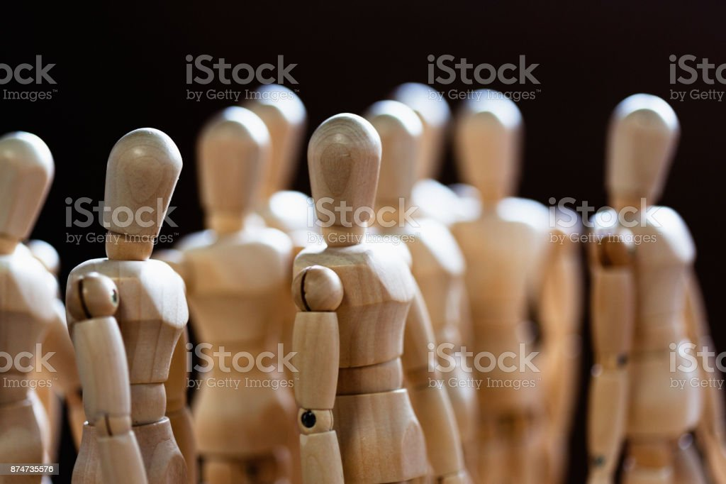 Crowd of brightly lit miniature wooden figures stock photo