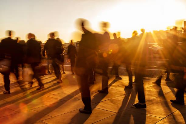menge von geschäftsleuten bei sonnenuntergang, london, england - hauptverkehrszeit stock-fotos und bilder