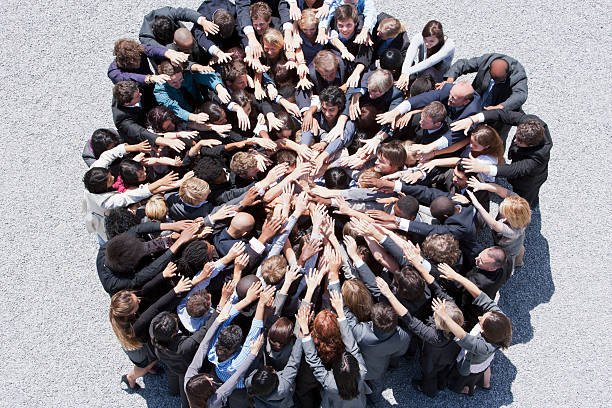 Crowd of business people forming huddle with extended arms  dedicated stock pictures, royalty-free photos & images