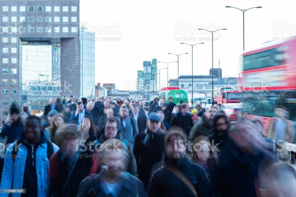 Crowd Of Commuters Walking To Work Across London Bridge UK With...