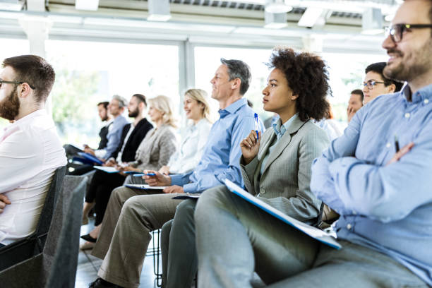 Crowd of entrepreneurs paying attention on business seminar in board room. Large group of business people attending a seminar in a board room. attending stock pictures, royalty-free photos & images
