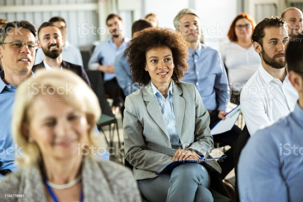 Large group of business people attending a seminar in a board room....