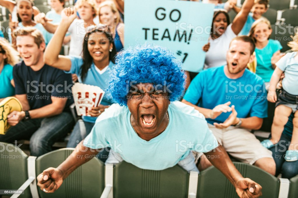 Crowd of fans cheering from stadium bleachers stock photo