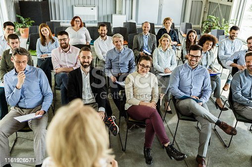 istock Crowd of happy business people attending a seminar in board room. 1161926571