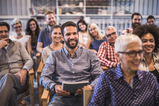 Crowd of happy freelancers attending a professional training class in board room. Large group of happy entrepreneurs attending a business conference in board room. Focus is on young man with beard. attending stock pictures, royalty-free photos & images