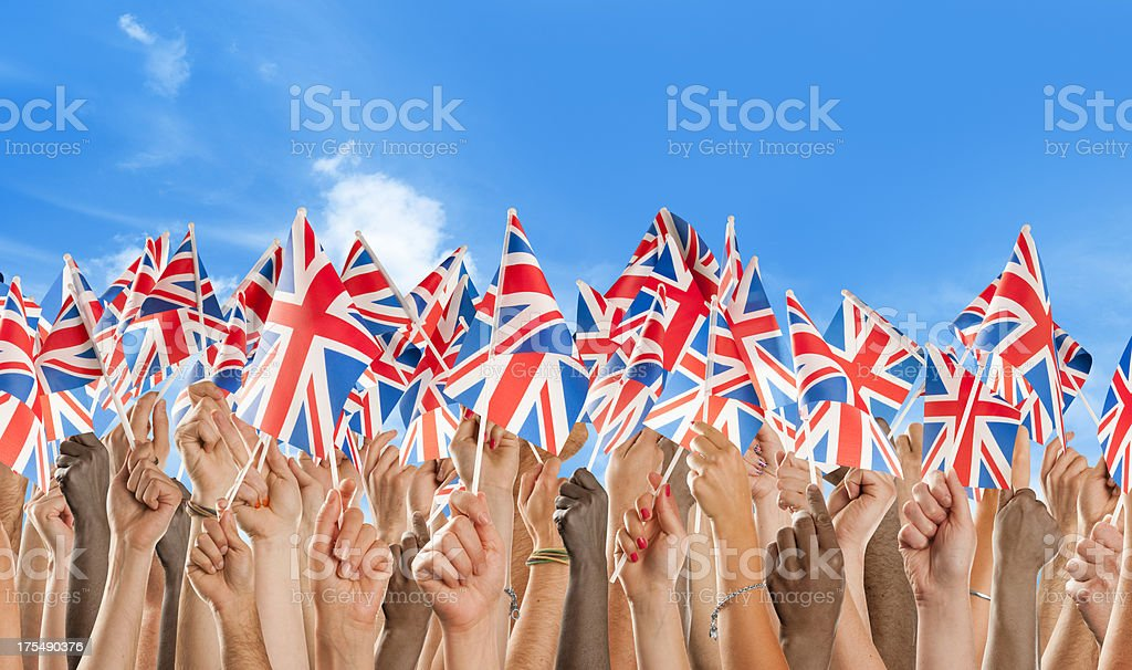 Crowd of mixed nationalities waving union jack flags stock photo
