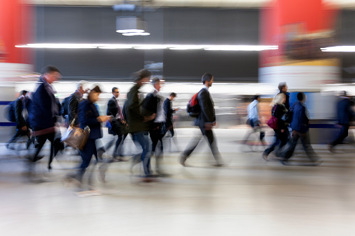 Crowd of Motion Blurred Businesspeople Walking in Subway Station, London