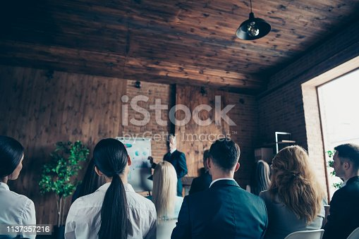 istock Crowd of nice stylish trendy serious sharks audience attending corporate forum listening top management company ceo boss chief specialist expert at industrial loft interior work place space indoors 1137357216